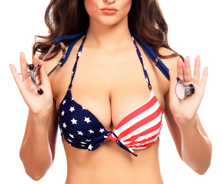 big boobs: Mujer atractiva en traje de baño con los colores de la bandera USA tiene un estetoscopio, aislado en blanco