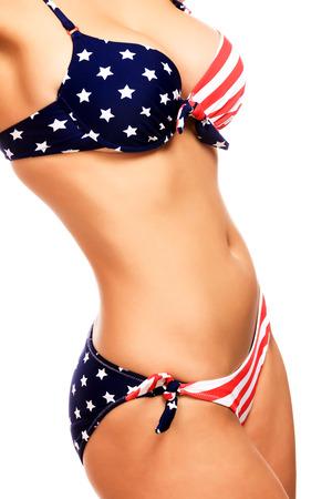 tetas: Mujer atractiva en traje de baño con los colores de la bandera USA, aislado en blanco