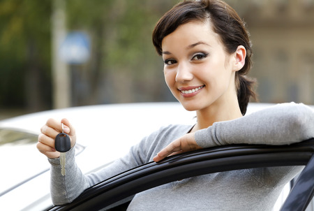 sell car: Pretty girl showing the car key