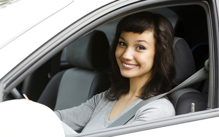 drive car: Pretty female driver in a white car Stock Photo