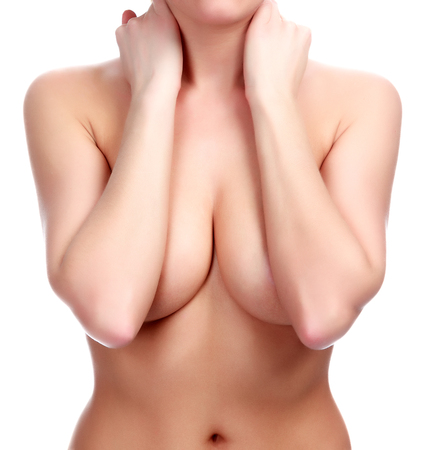 Beautiful breasts: Woman covers her breasts by hands, isolated on white