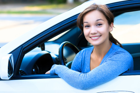 Girl in a car smiling to you. Stock Photo