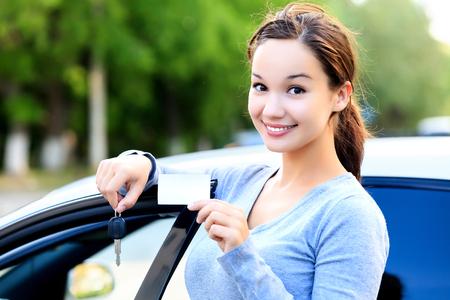chofer: La mujer se coloca al lado de un coche y muestra las llaves y tarjeta blanca Foto de archivo
