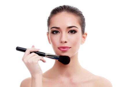 Pretty woman with makeup brush, isolated on white