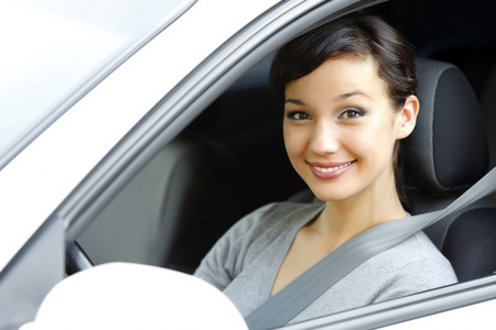 female driver: Cute asian female driver in white car smiling to you. Stock Photo