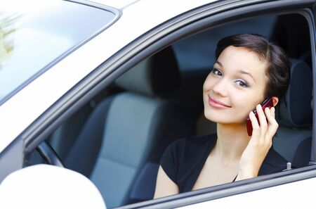 mobile telephone: Woman sitting in a car and talking by mobile telephone