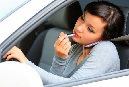mobile telephone: Pretty female driver talking by mobile telephone and doing make-up. Stock Photo
