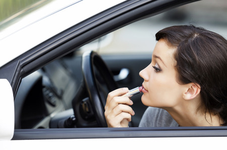 applying: Pretty young woman in a car doing makeup while standing in a road jam