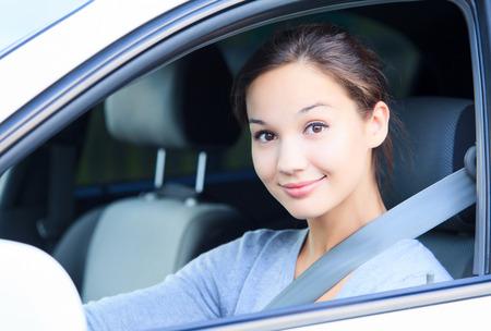 Muchacha en un coche sonriendo a usted.