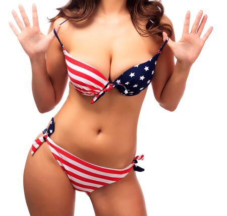 tetas: Señora atractiva que desgasta traje de baño con los colores de la bandera USA, aislado en blanco