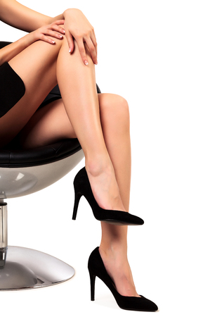 Frau mit langen Beinen auf einem Stuhl sitzt, isoliert auf weißem Hintergrund
