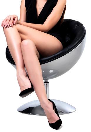 pies sexis: Mujer con las piernas largas que se sientan en una silla, aislado en fondo blanco Foto de archivo