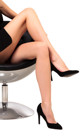 skirts: Woman with long legs sitting in a chair, isolated on white background