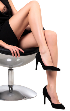 secretary: Woman with long legs sitting in a chair, isolated on white background