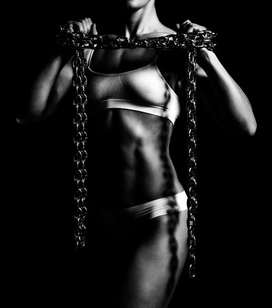 sexy female: Sports woman with a thick chain, isolated on a black background Stock Photo