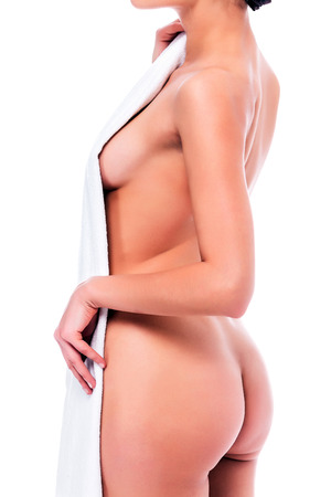 nude female buttocks: Naked woman holds a white towel, isolated on a white background