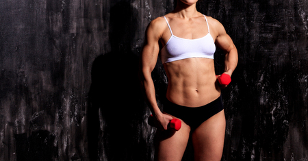 strong woman: Strong woman with red barbells, dark background Stock Photo