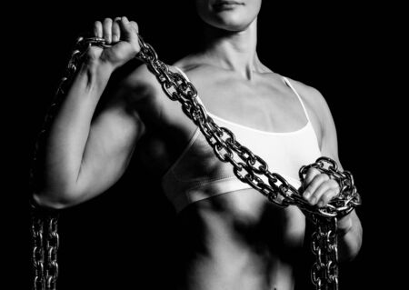 female sexy chains: Strong woman with a thick iron chain, black background
