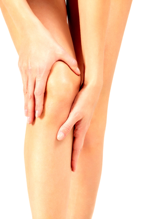 Pain in a knee, woman touches her knee, isolated on white background Stock Photo