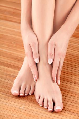 belles jambes: Femme touche ses pieds Banque d'images