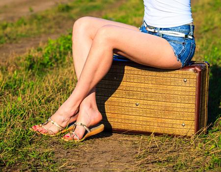 belles jambes: Femme assise sur la valise sur la route de campagne