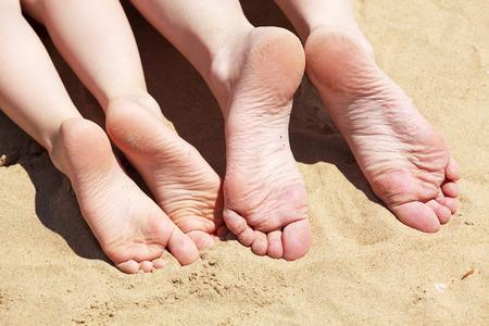 Füße der Mutter und ihrem Kind in den Sand