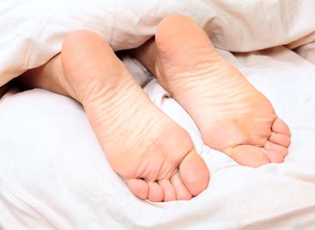 los pies desnudos femeninos debajo de la manta