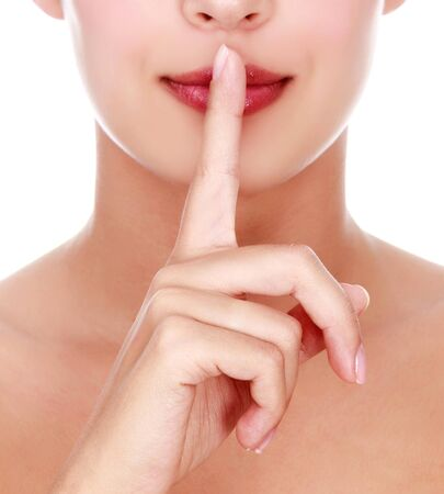 Secret. beautiful girl with her finger near the lips, isolated on white background photo