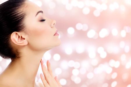 Jong vrouwtje raakt haar nek op een abstracte achtergrond met vage lichten