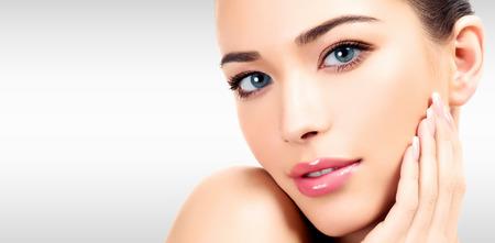 Portrait en gros plan d'une belle femme avec un visage de beauté et une peau douce propre et lisse, un maquillage doux. Fond d'acier gris avec un lieu pour votre information