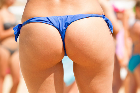 Beautiful buttocks of a tanned woman. Summer beach holidays concept. Closeup shot