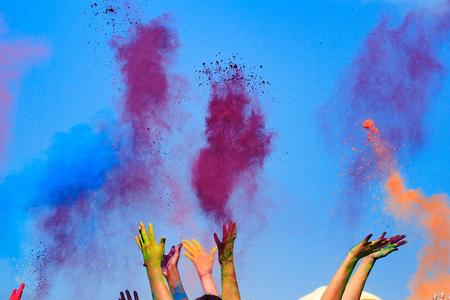 Bij de kleur Holi Festival, handen in de lucht, blauwe lucht achter