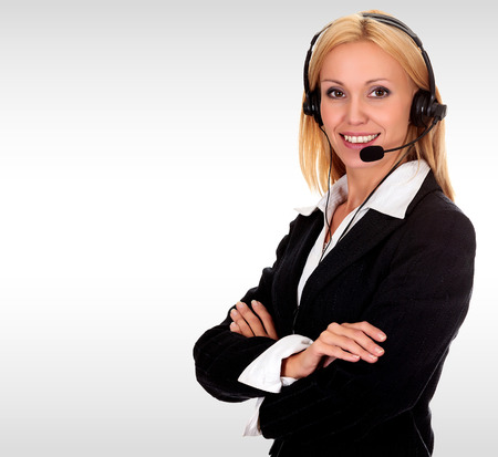 Pretty business woman with a headset against a grey background with copyspace photo