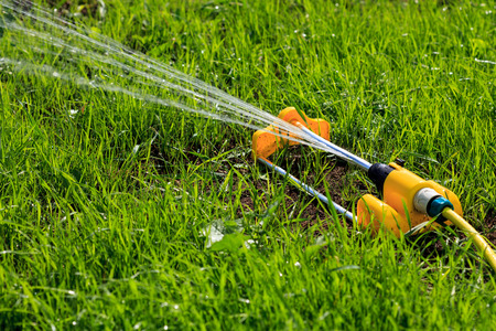 spaying: Closeup shot of yellow lawn sprinkler spaying water over green grass field. Irrigation system Stock Photo