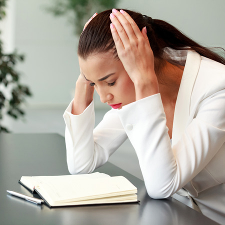 Tired young woman with headache in an office