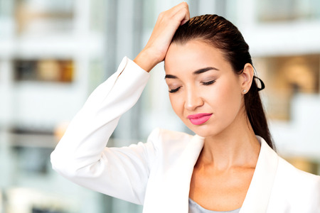Woman with a headache in an office. Woman forgot something.