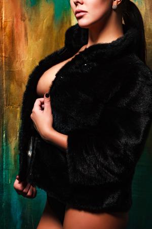 Sexy woman wearing black fur coat
