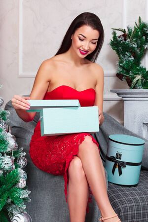 Closeup shot of young woman in red dress who opens gift box