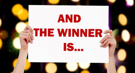 Y el ganador es ... manos femeninas que sostienen un cartel con luces abstractas fondo bokeh