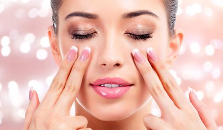 Hübsche Frau, die ihr Gesicht, Hautbehandlungskonzept massiert. Abstrakter Hintergrund mit unscharfen Lichtern