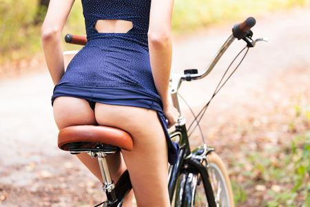 그녀의 아름다운 엉덩이를 보여주는 자전거에 젊은 여자, 근접 촬영 스톡 콘텐츠