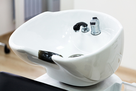 Closeup shot of chair with bowl for hair washing in hairdresser salon. Main focus is on the faucet 스톡 콘텐츠