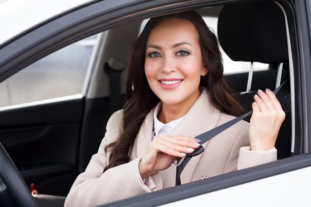 Portrait of young smiling, happy, pretty woman driver pulling on seatbelt inside white car.