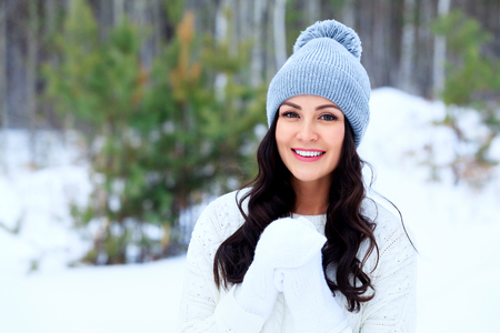 Young happy woman posing in a winter forest and smiling to you