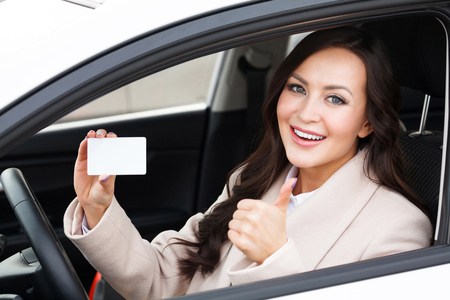 Beautiful young girl sitting in white car showing an empty white card and thumbs up hand sign
