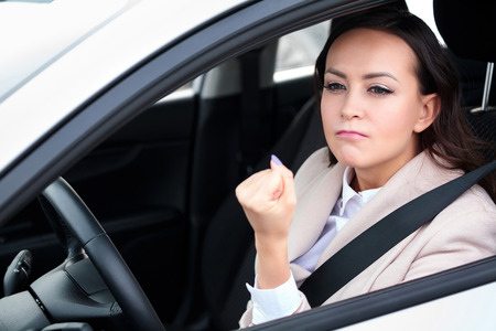 Boorishness on the road. Young woman is showing her fist to someone Фото со стока