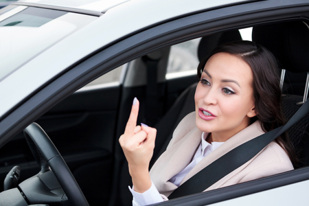 Pretty woman driver is showing middle finger to someone, boorishness on the roads.