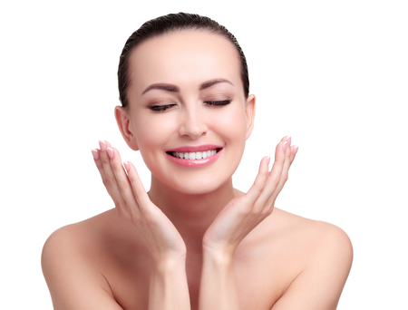 Joven mujer bonita feliz con piel suave y limpia está posando sobre fondo blanco, aislado