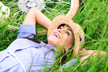 Happy woman lying on a green grass and smiling Imagens