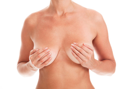 Naked woman covers her breasts by hands, isolated on white background Stock Photo